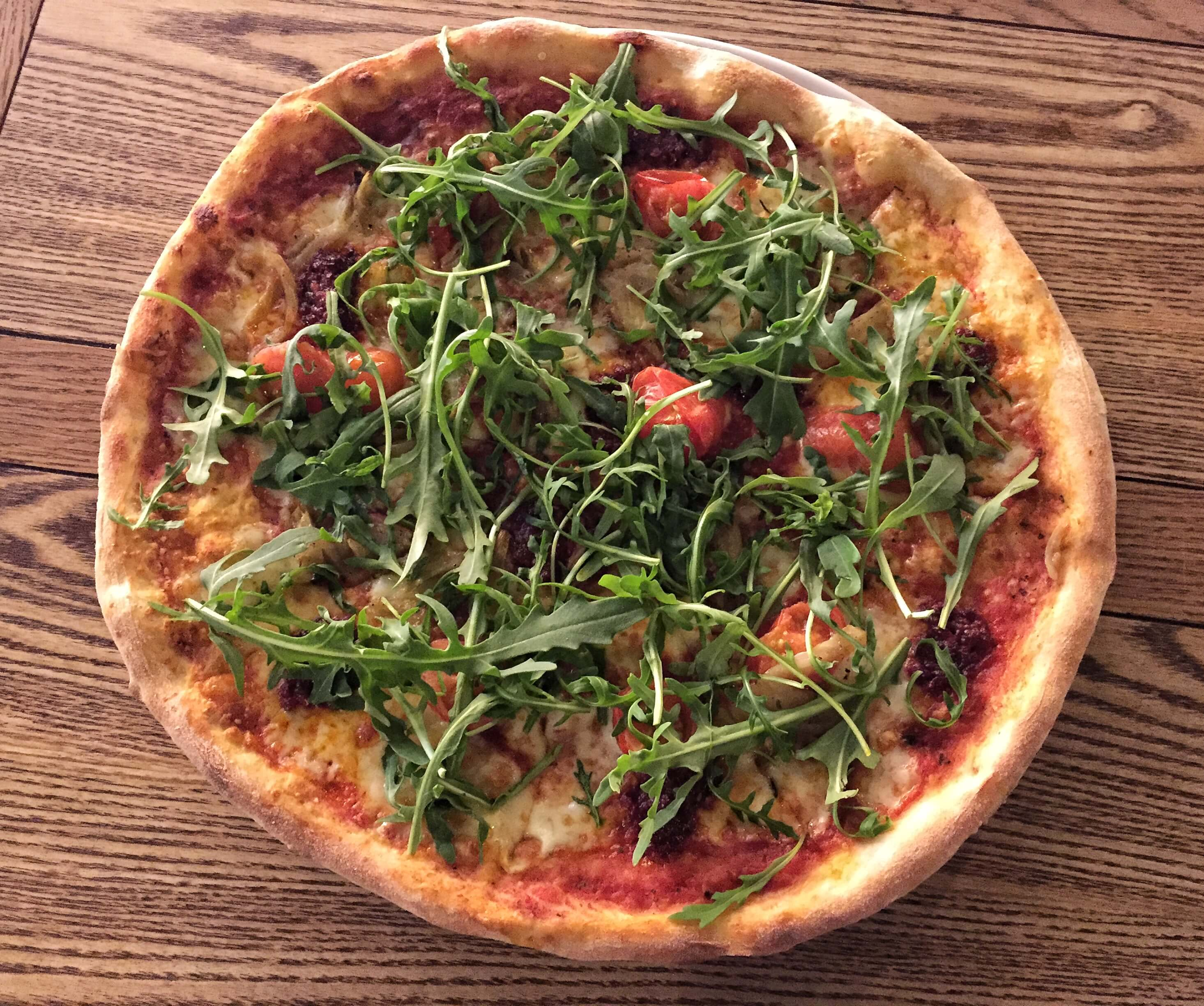 Pizza with 'nduja, cherry tomatoes and rocket at The Coach and Horses, Clapham, London