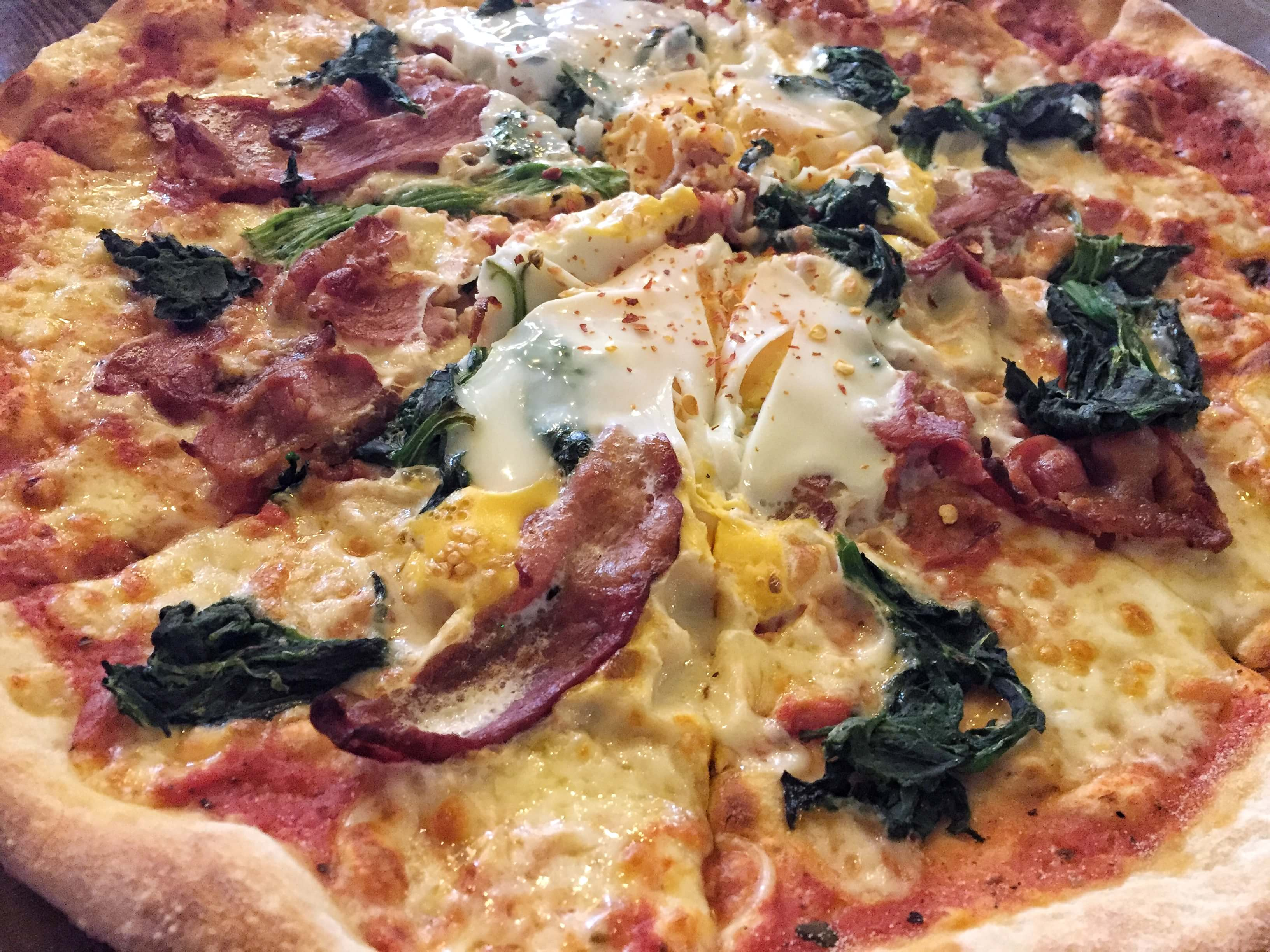 Pizza with bacon, egg, spinach and chilli at The Coach and Horses, Clapham, London
