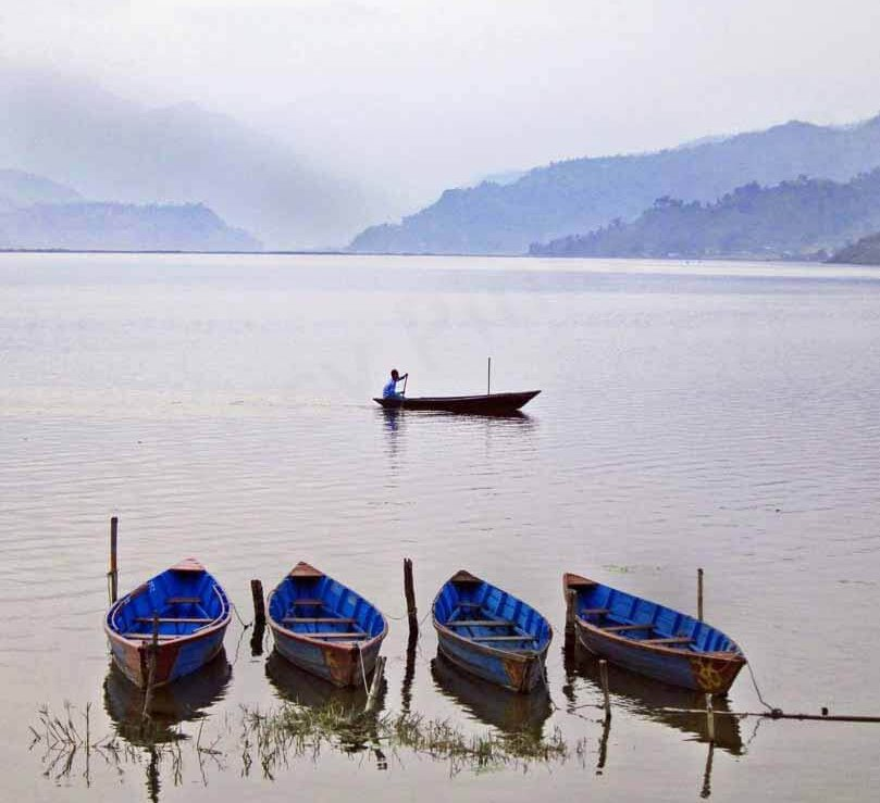 Travel in Nepal: A man in a boat sailing across Lake Fewa in Pokhara, Nepal