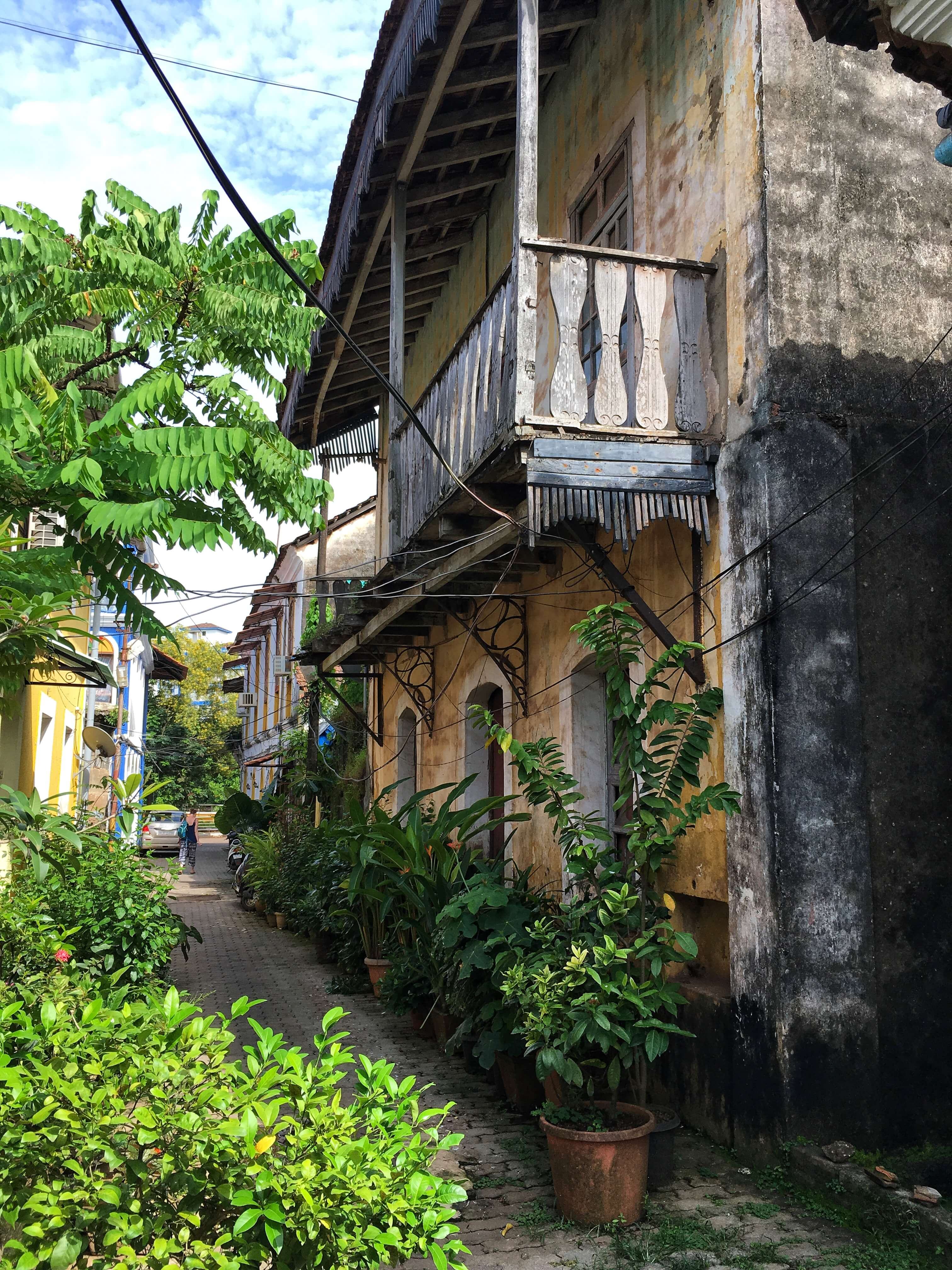 Old building with wooden balcony and plants in Panaji, Goa
