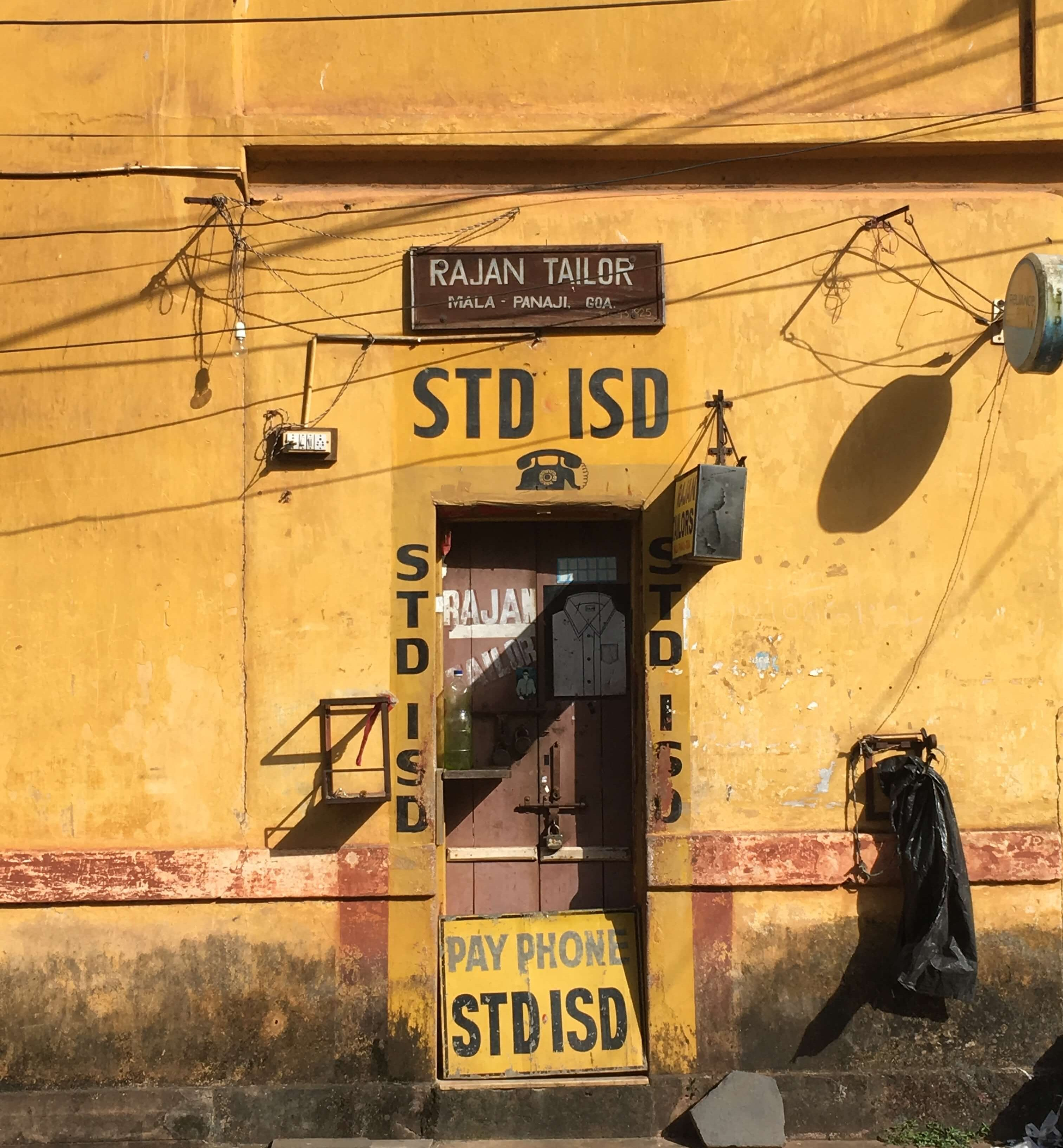 Tailor and pay phone in a yellow building in Panaji, Goa