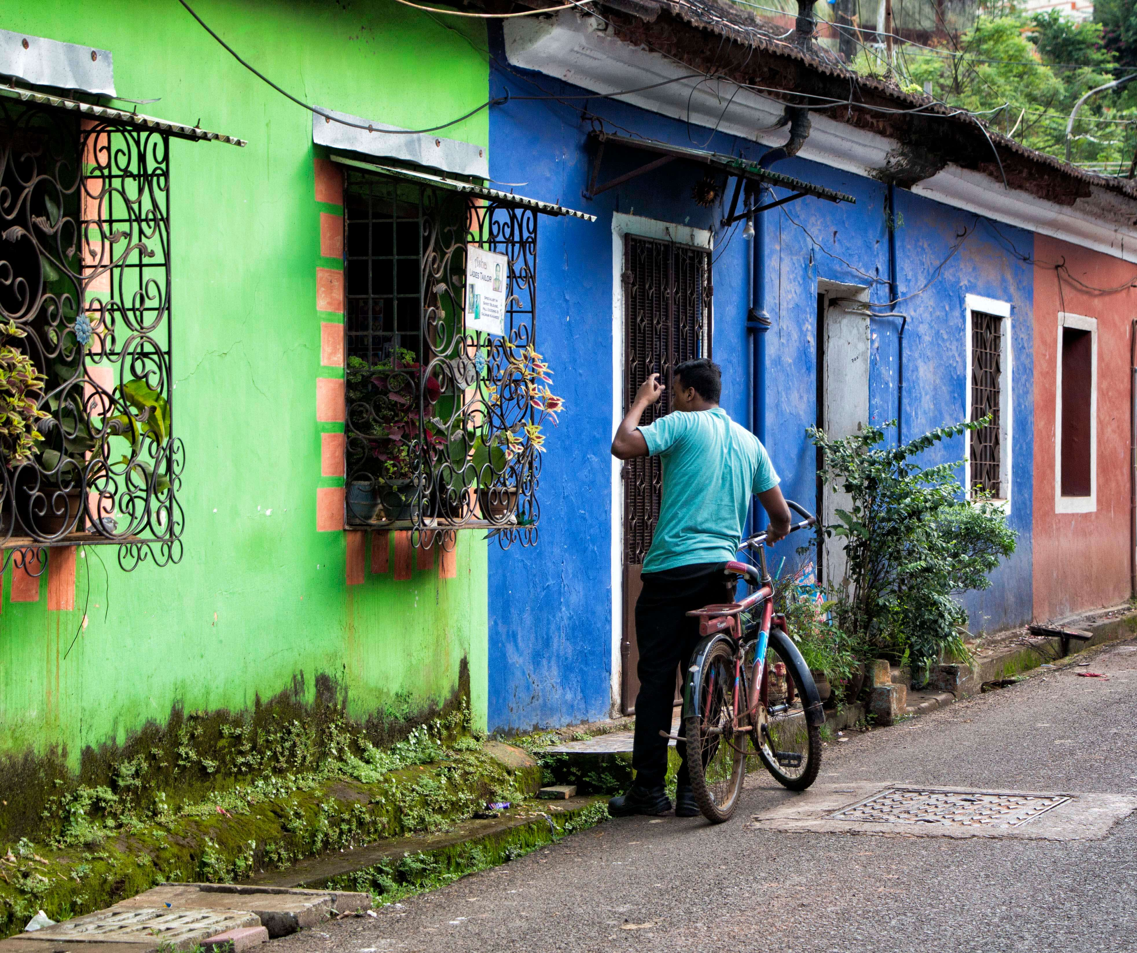 Man with bicycle outside shop in Panaji, Goa