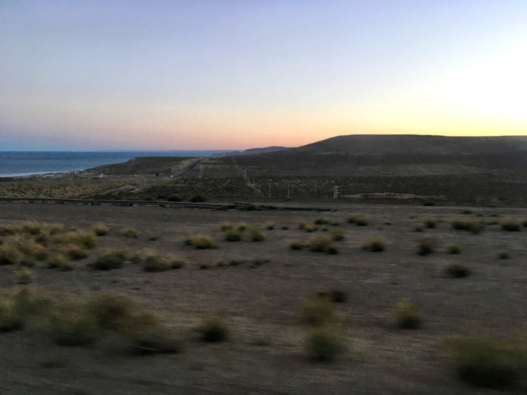 Sun setting over the Patagonian plains with the ocean in the background